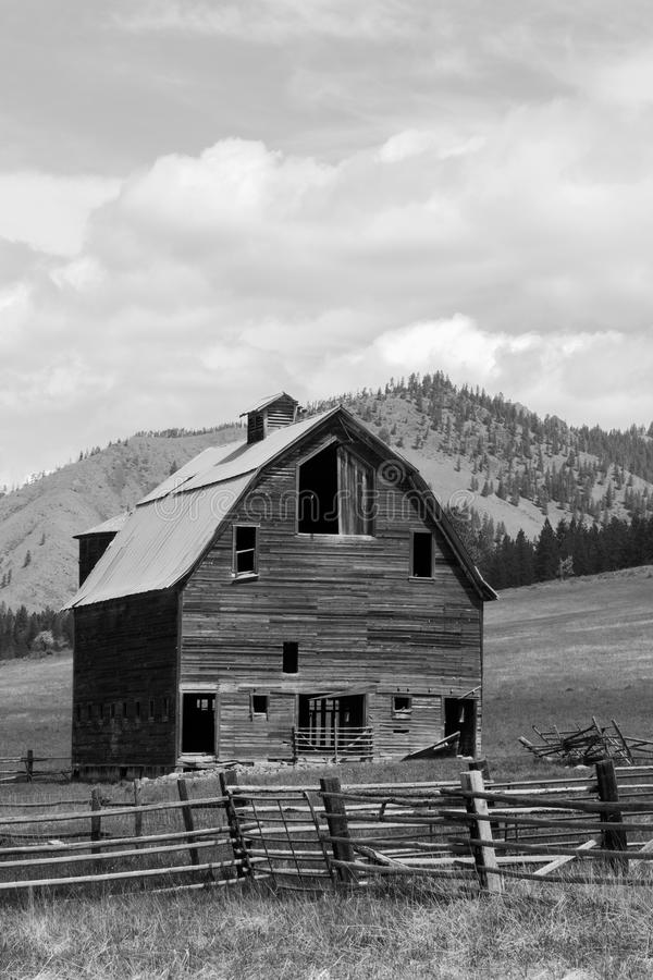 Old barn and abandoned homestead on a green grassy hillside. A beautiful old barn and homestead with fence line and abandoned orchard along the grassy hill that stock photography