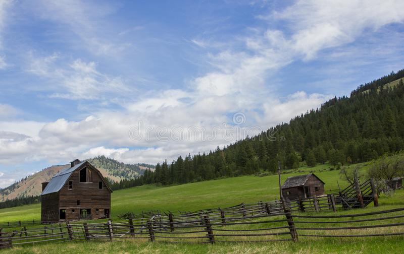 Old barn and abandoned homestead on a green grassy hillside. A beautiful old barn and homestead with fence line and abandoned orchard along the grassy hill that stock photos