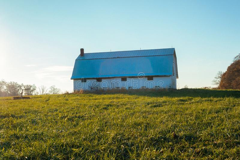 Old barn on farm in Indiana countryside. A beautiful white barn rises above field of green grass in Southern Indiana countryside near Sunman stock photo