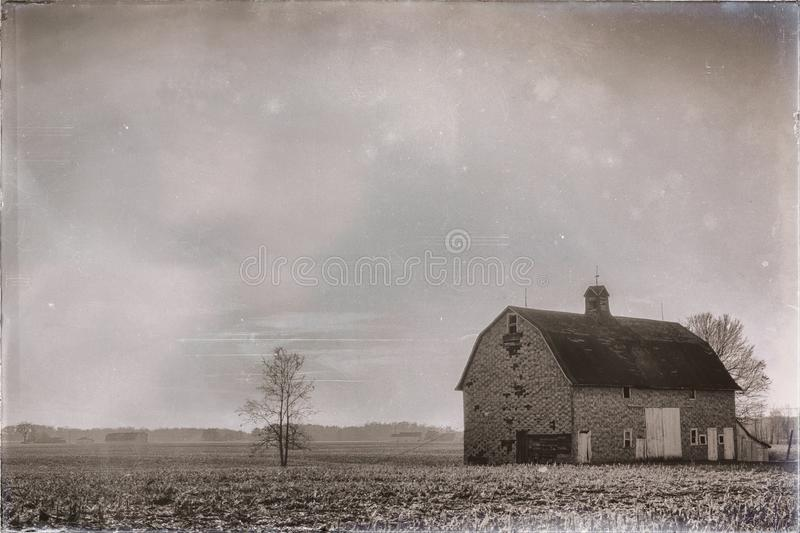 Old barn on farm in Indiana countryside black and white. Old fashioned style photo of very old barn rises above field of harvested crops in southern Indiana farm