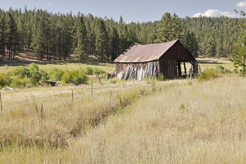 Old Barn On Oregon Ranch. An old pioneer barn with a rusting metal roof in a grassy meadow on an Oregon ranch is gradually falling into disrepair royalty free stock image