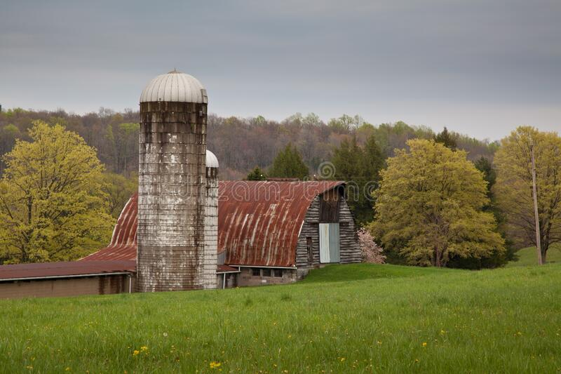 Old barn and a silo surrounded by trees and green fields in early spring in Pennsylvania. An old barn and a silo surrounded by trees and green fields in early stock photo