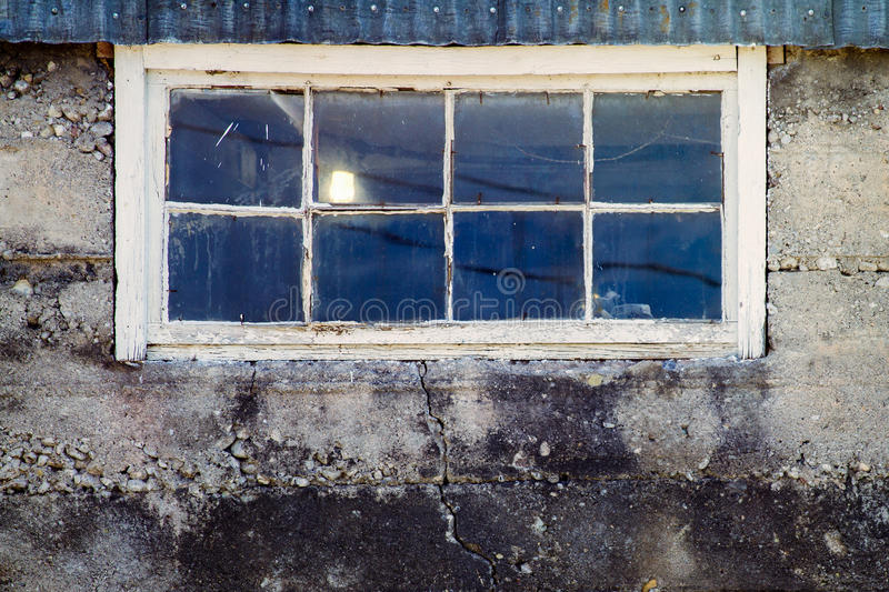 Old barn window. A single light shines through an old barn window that has been weathered with time stock photography