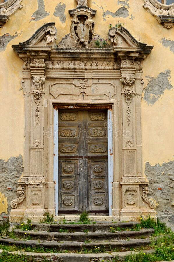 Old baroque church in Milazzo, Sicily. Old baroque church with crumbling plaster. An old wooden door with an elaborate decoration on the door royalty free stock photos