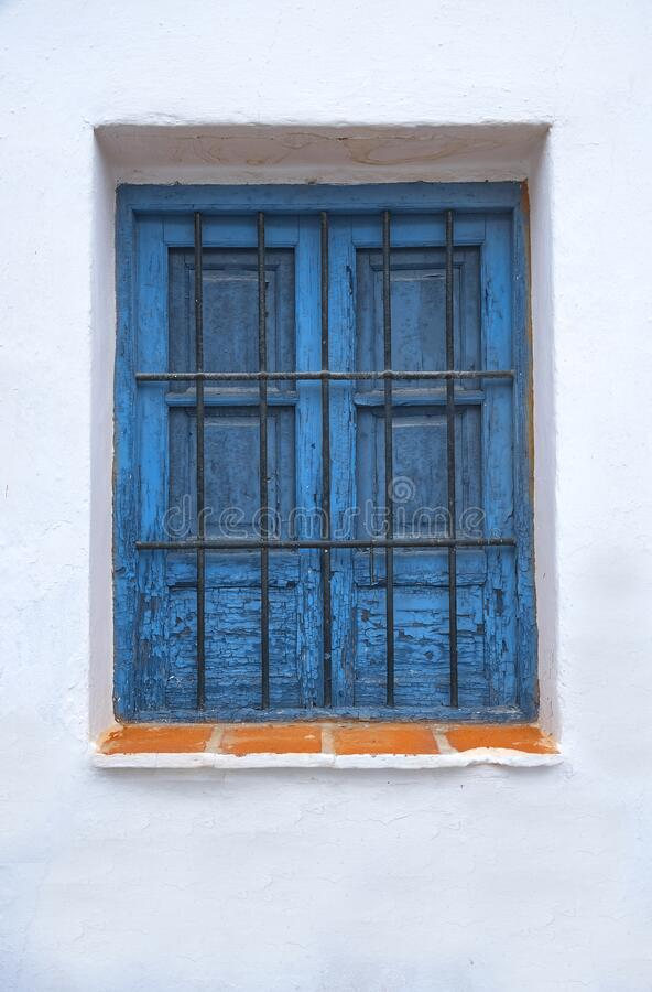 Old barred window shutters, with peeling blue paint. stock images