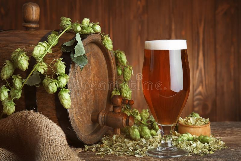 Old barrel, glass of dark beer and hop branch on table against wooden background stock photos