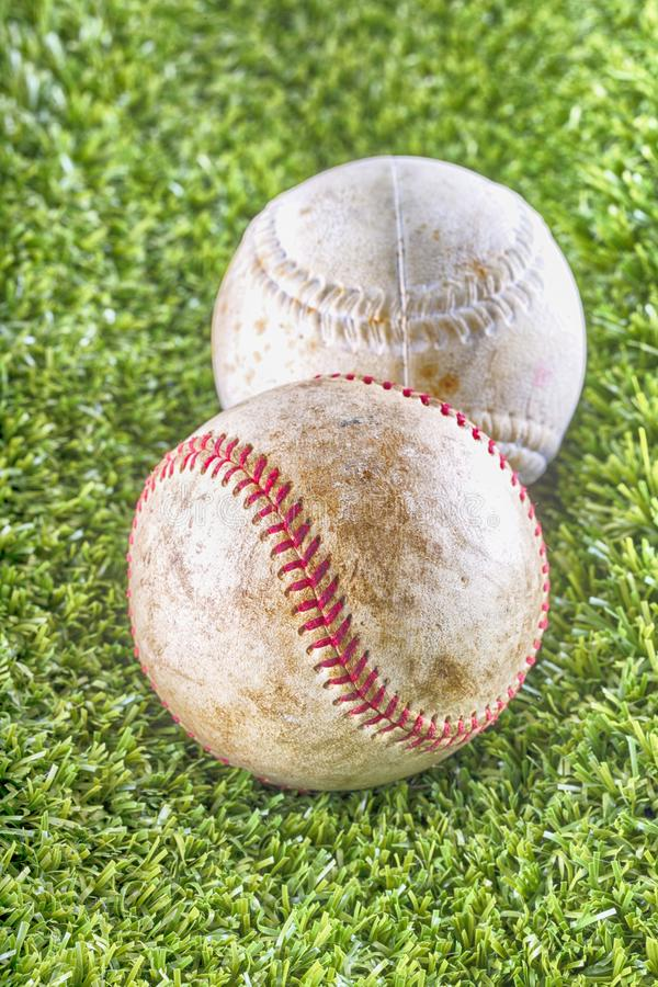 Old baseballs over synthetic grass royalty free stock photography