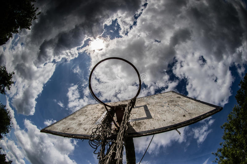 Old basketball court, basket, snatched netting against the sky. And clouds royalty free stock photography
