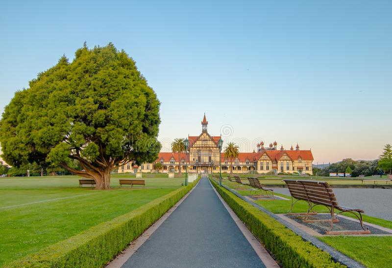 Grand Estate. An old bathhouse in Rotorua, New Zealand with a pathway leading to the house and a grand green lawn in the foreground with a lone huge tree off to royalty free stock image