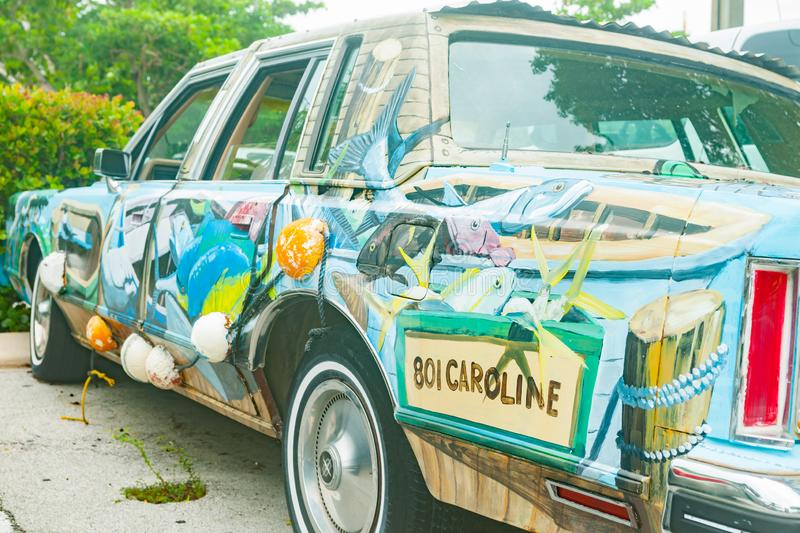 Old battered car painted with wildlife and floral scene royalty free stock image