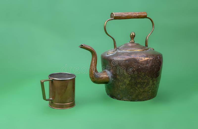 Old and battered copper kettle. View of a brass and copper kettle and mug on a green background royalty free stock photo