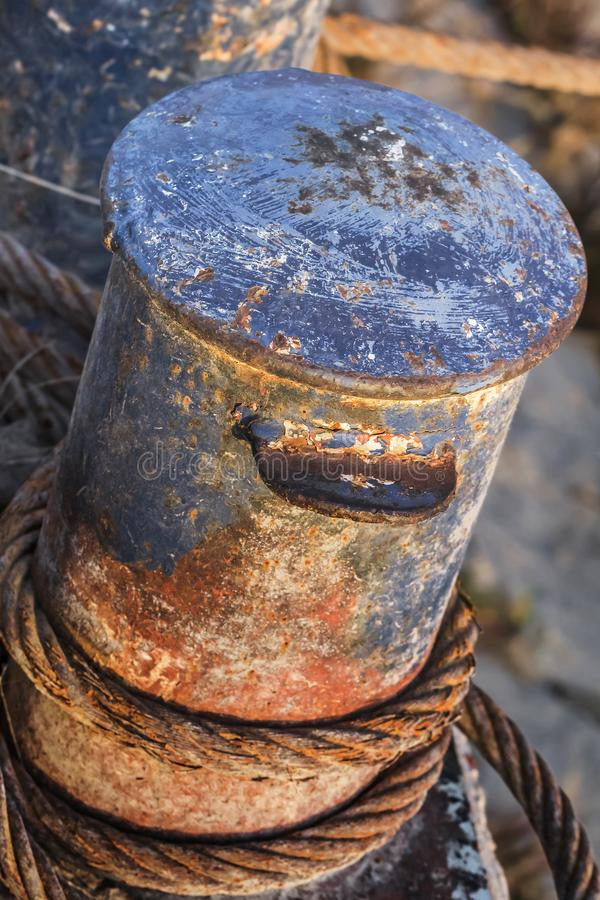 Old Battered Rusty Iron Bollard With Coiled Corroded Steel Cable.  stock photography