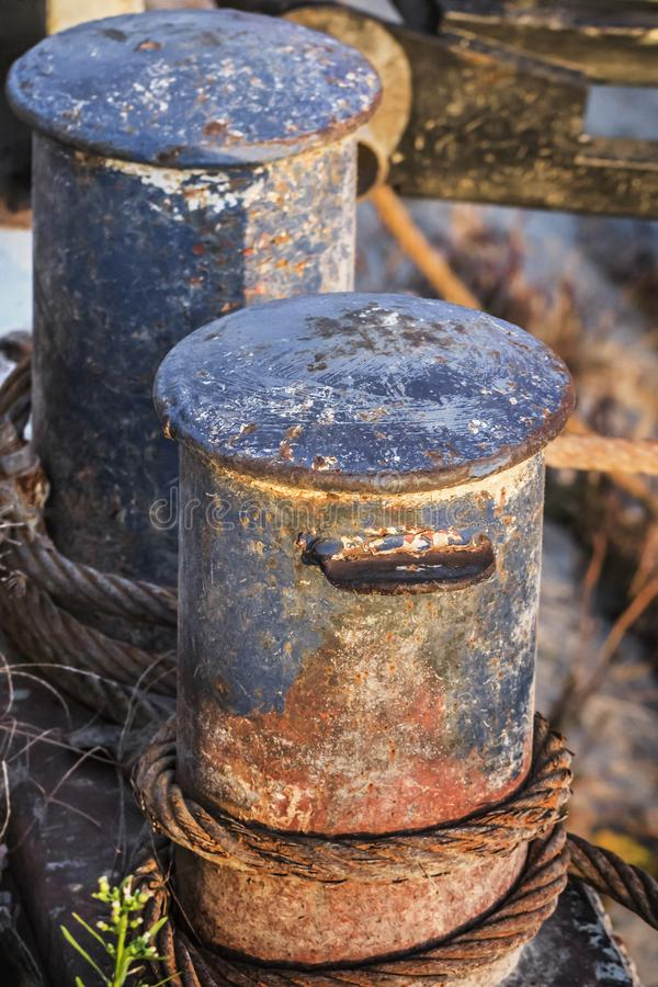 Old Battered Rusty Iron Bollards With Coiled Corroded Steel Cable.  royalty free stock images