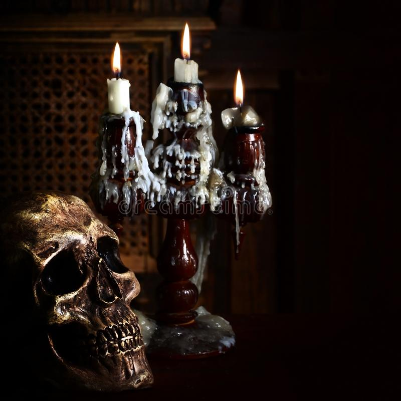 Old battered skull lies with an antique wooden candlestick. The concept of black magic, services from sorcerers and magicians royalty free stock image