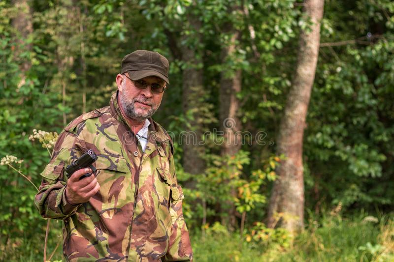 Old bearded thug with a gun in his hand. Russian gangster in camouflage uniform in the forest. Forest brother with a gun stock photos