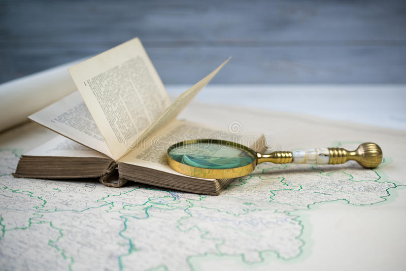 Old beautiful golden magnify glass on ancient book and old map. Old beautiful golden magnify glass on open ancient book and old map stock images