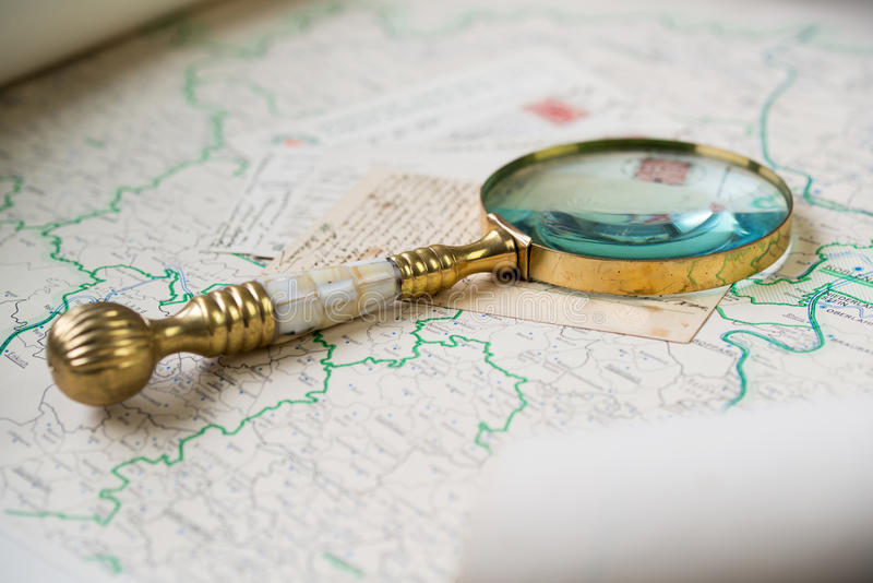 Old beautiful golden magnify glass on ancient post cards and old map. Old beautiful golden magnify glass on ancient post cards and old Germany map stock photography