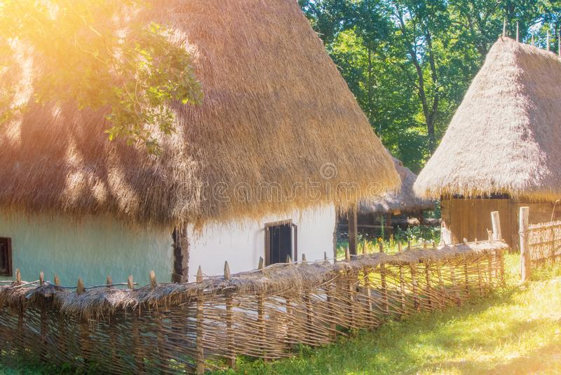Old beautiful traditional romanian ukranian farm village house w. Ith white walls, roof covered with straw, wooden fence wickered by hand and a garden with royalty free stock photo