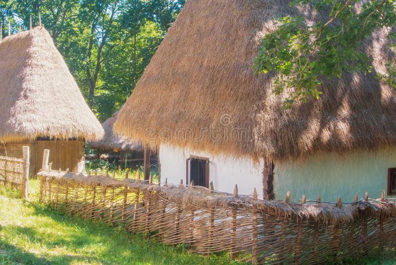 Old beautiful traditional romanian ukranian farm village house w. Ith white walls, roof covered with straw, wooden fence wickered by hand and a garden with royalty free stock image
