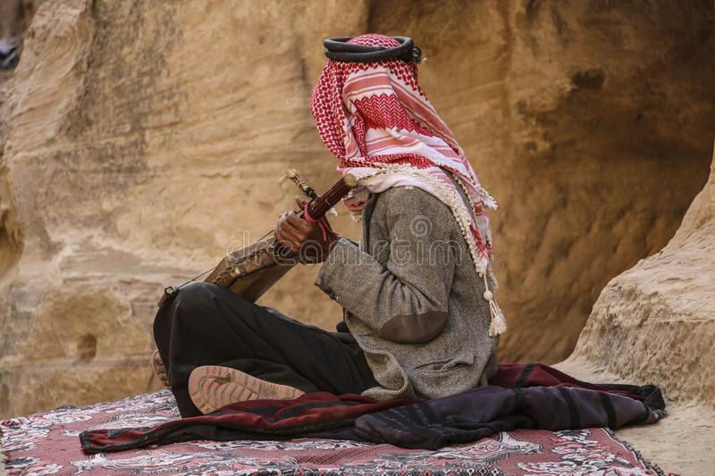 Old bedouin in the keffiyeh plays on the national musical instrument of Jordan,Petra, Jordan royalty free stock photography