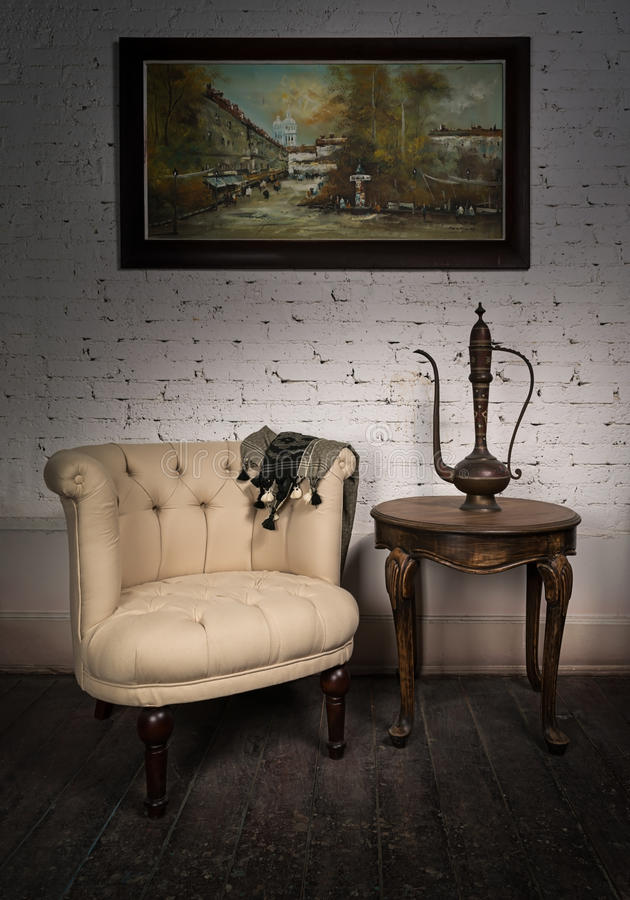 Old beige armchair, brass teapot, framed painting and antique table royalty free stock images