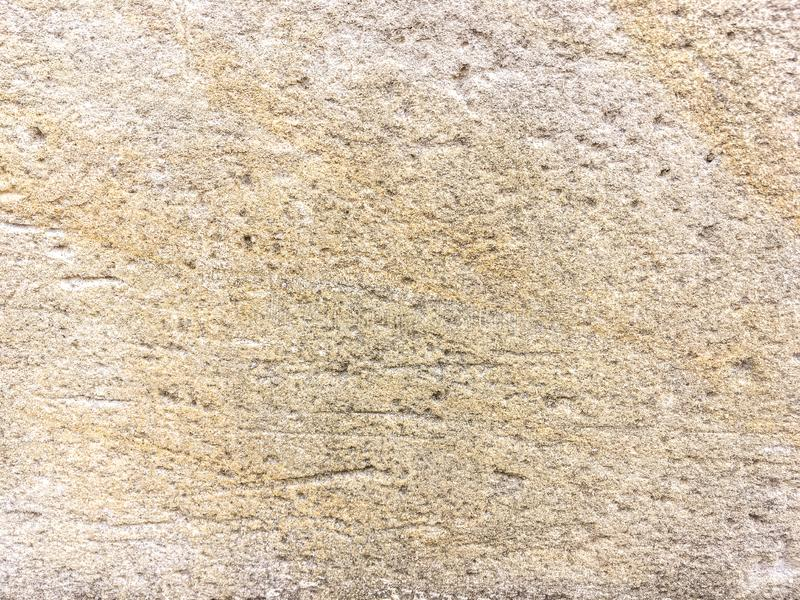 Old beige cracked limestone wall, close up. Texture of brown ancient stone, background stock image