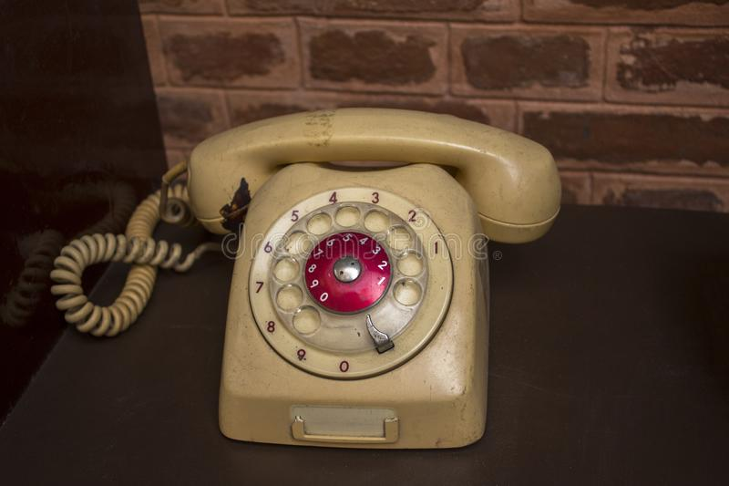 A old beige vintage dial telephone on a brown table. Old beige vintage dial telephone on a brown table royalty free stock photos