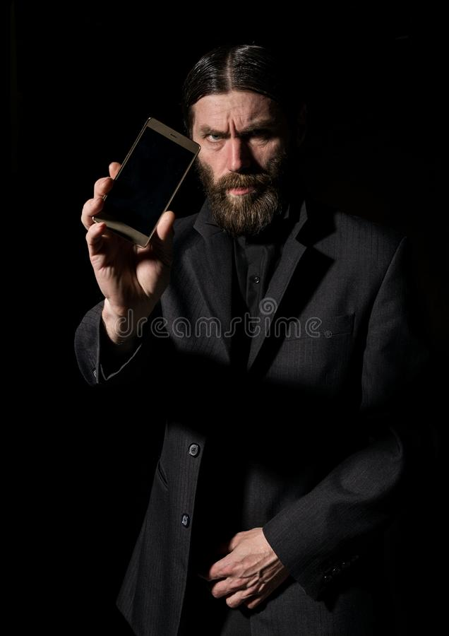 Strange bearded senior priest with a smartphone, bearded old man is calling on a dark background stock images
