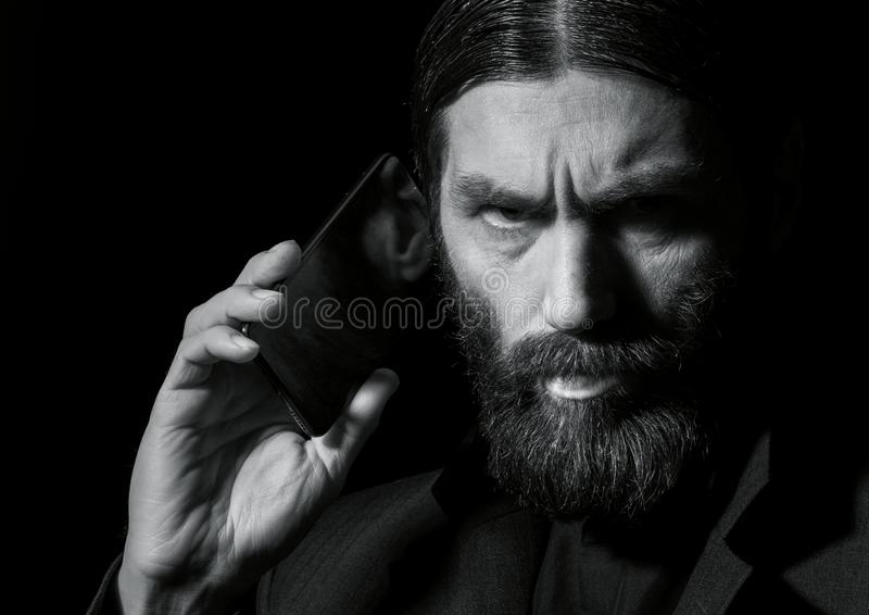 Strange bearded senior priest with a smartphone, bearded old man is calling on a dark background. black and white stock photography