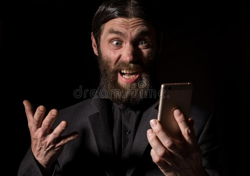 Old believer senior priest with a smartphone, bearded old man is calling on a dark background royalty free stock photo