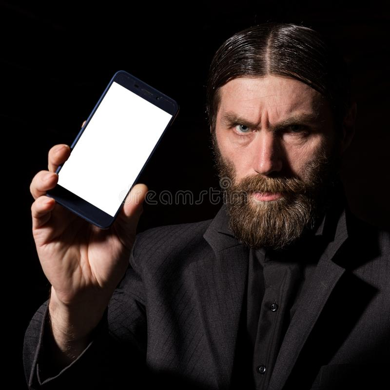 Old believer senior priest with a smartphone, bearded old man is calling on a dark background royalty free stock images