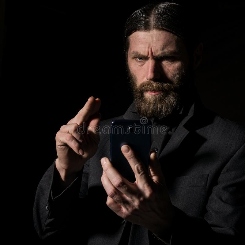 Old believer senior priest with a smartphone, bearded old man is calling on a dark background stock photos
