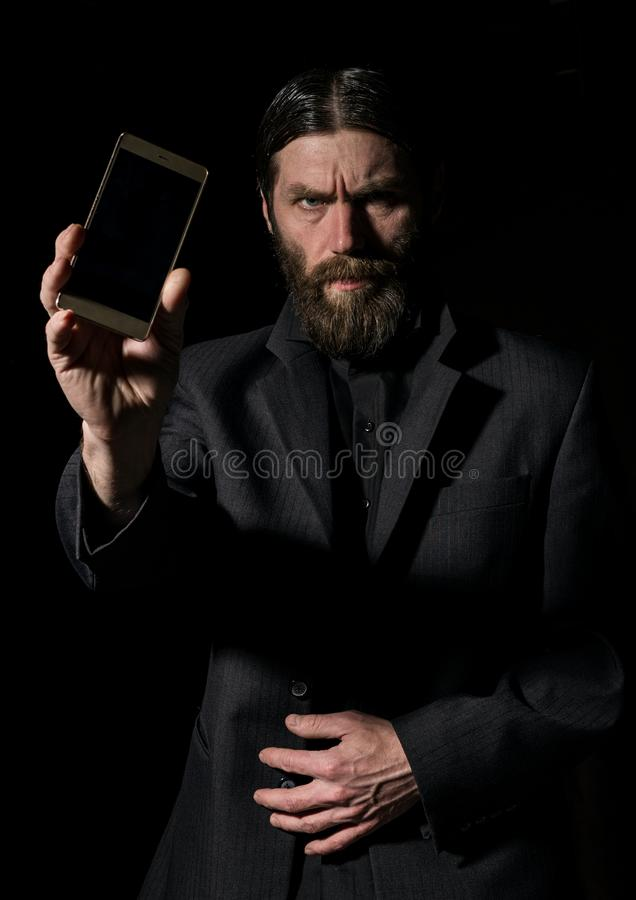 Old believer senior priest with a smartphone, bearded old man is calling on a dark background stock photography