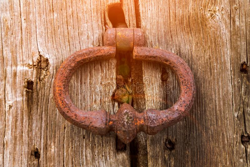 Old bell at the door, hand knocks on the wooden door. Old bell at the door, hand knocks on the wooden stock photography
