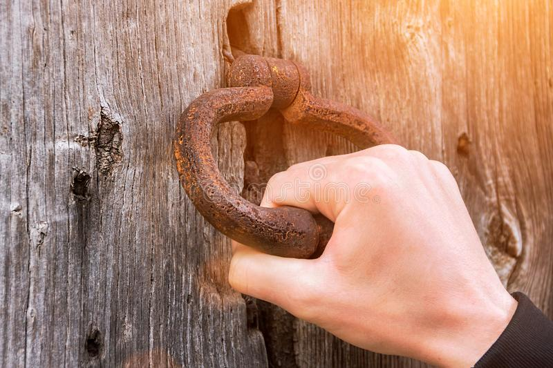 Old bell at the door, hand knocks on the wooden door. Old bell at the door, hand knocks on the wooden royalty free stock images