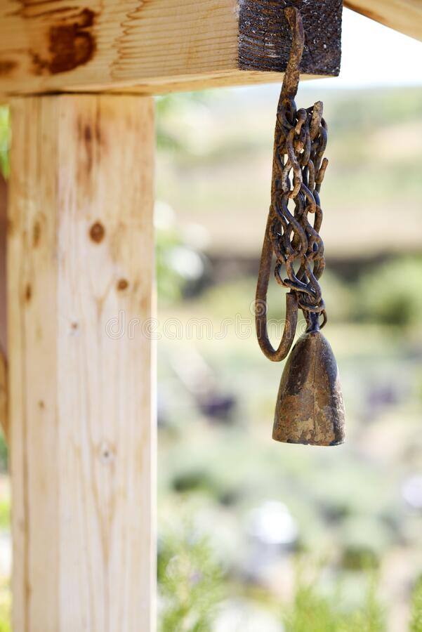 Old bell hanging. From the wooden beam from the house royalty free stock photography