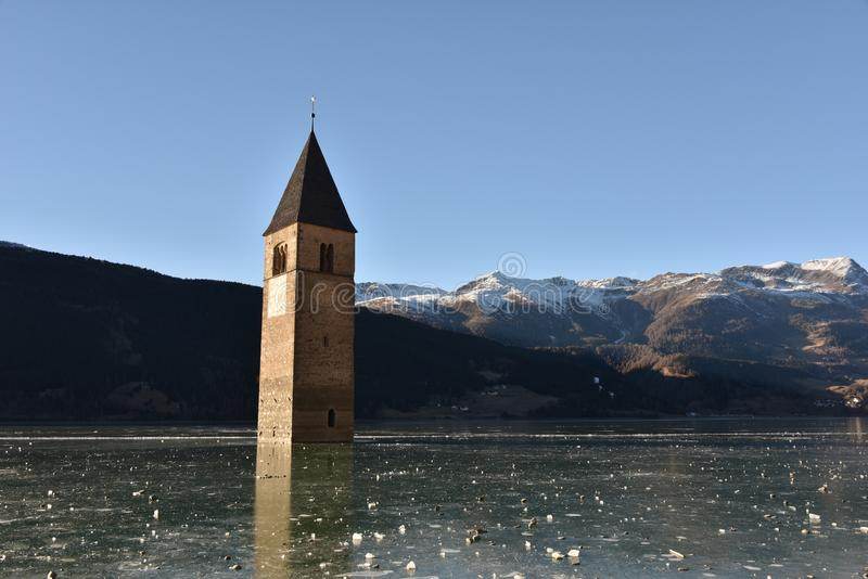 Old bell tower in the Lake Resia surrounded by mountains covered in the snow in Italy royalty free stock photo
