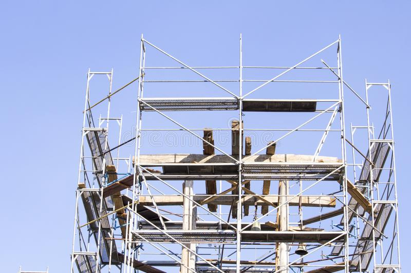 The old bell tower. Restoration of the old bell tower. Scaffolding. stock images