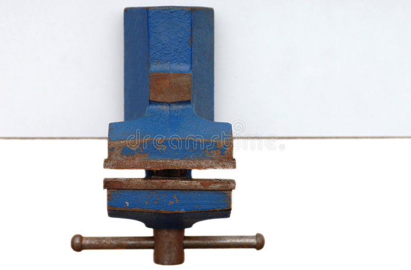 Old bench vice. On table, isolated stock photo