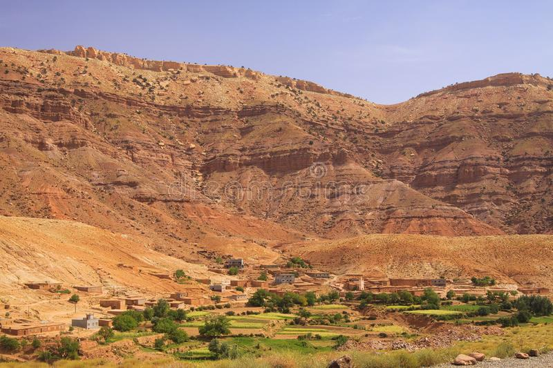 Old berber village oasis with houses build of clay bricks in front of impressive high rugged red mountain face, Gorges du Dades, royalty free stock photography