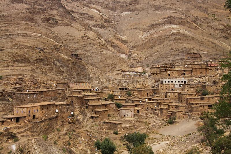 Old berber village oasis with houses build of clay bricks in front of impressive high rugged red mountain face royalty free stock images