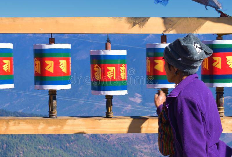Old Bhutanese lady and Old wooden Tibetan prayer wheels at Chele la pass , Bhutan stock images