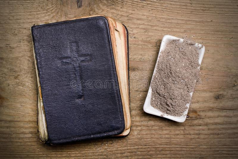Old Bible, Cross and ash on wooden background - Ash Wednesday royalty free stock photos