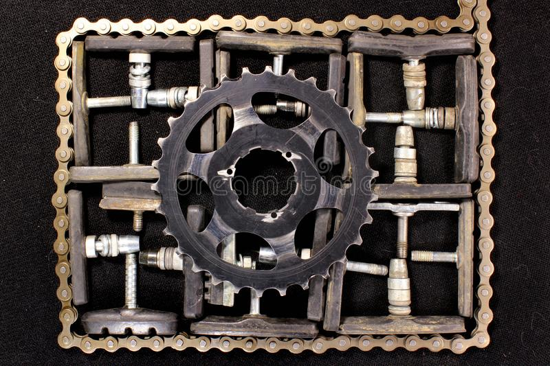 Old bicycle brake shoes with chain and sprocket on black background royalty free stock image