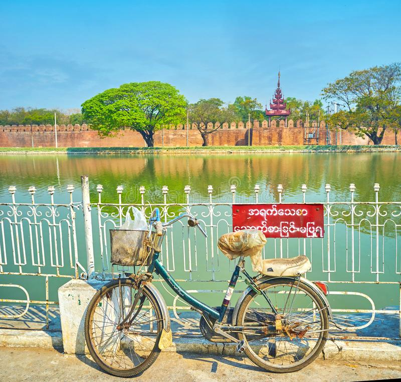 The old bicycle at the fence of the moat in Mandalay, Myanmar. MANDALAY, MYANMAR - FEBRUARY 23, 2018: The old bicycle parked at the fence of Royal Palace`s moat royalty free stock photography