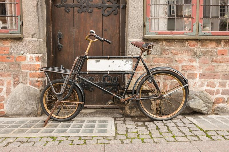 An old bicycle, in front of a brick wall and an old wooden door. The bicycle has a blank sign inside the frame. Old concept royalty free stock image