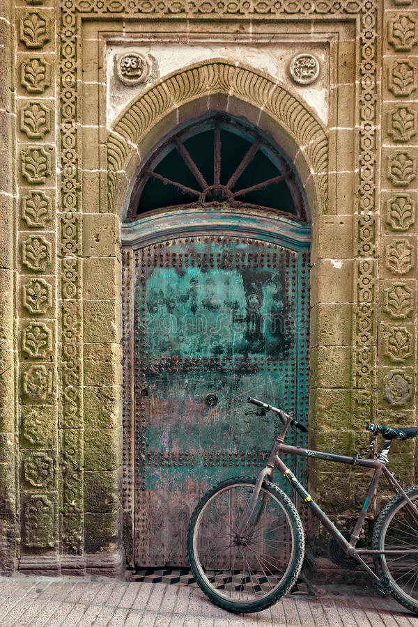 Old bicycle in front of a weathered door, Morocco stock photos