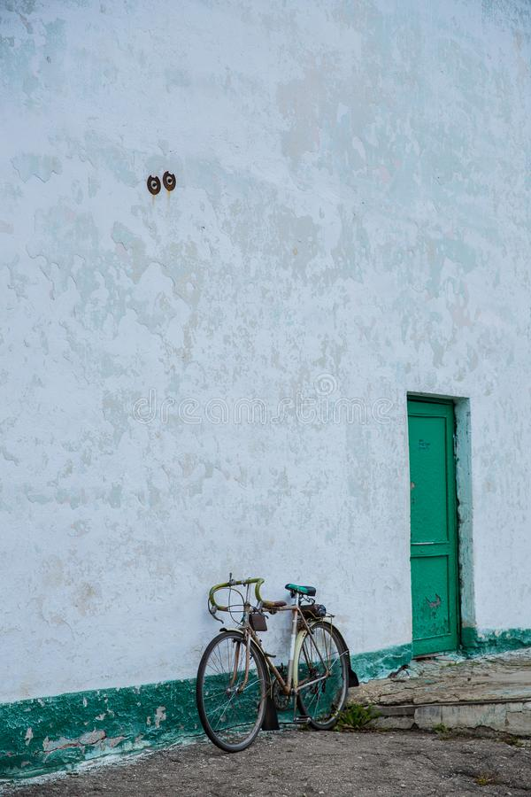 An old bicycle leaning against a dilapidated blue wall. royalty free stock photo