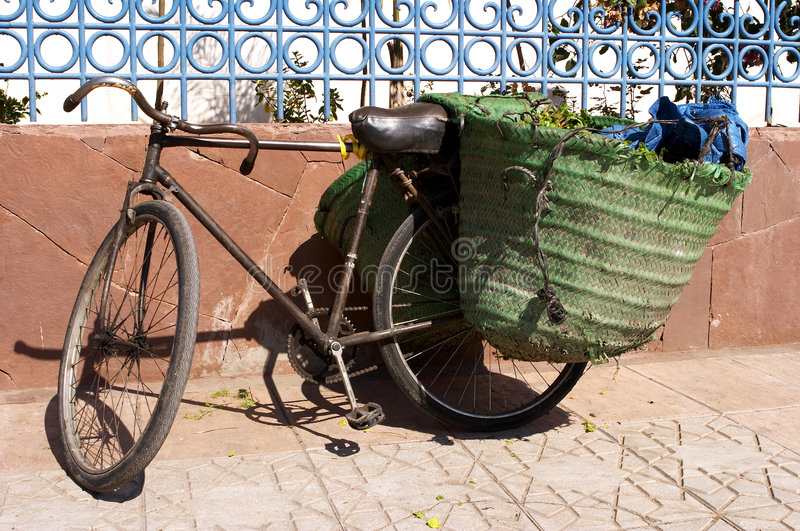 Old bicycle leaning against wall with panniers on the back stock image