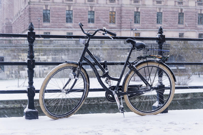 Old bicycle parked on a bridge in Stockholm. Old bicycle parked on a bridge in winter royalty free stock images
